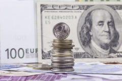 在钞票美元欧元背景的俄国硬币科比  图库摄影