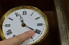 在钟针上的手指 免版税库存照片