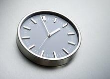 在钢墙壁上的金属时钟  库存图片