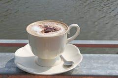 在钢河背景安置的加奶咖啡杯子 库存照片