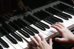 在钢琴的年轻手 图库摄影