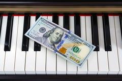在钢琴钥匙的一百元钞票 免版税图库摄影