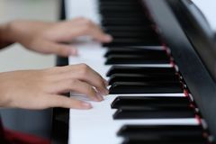 在钢琴钥匙的儿童手 免版税库存图片