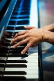 在钢琴钥匙的背景的钢琴演奏家手 库存照片