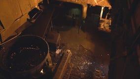 在钢铁厂熔炉的金属熔炼 英尺长度 在罐的顶视图变硬的金属在旁边洒并且发火花热 库存图片