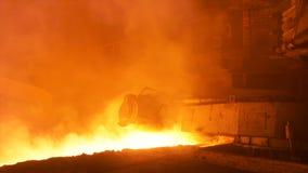 在钢铁厂的热的钢铁生产,冶金学概念 储蓄英尺长度 有流动的溶解的钢的热的商店在 免版税库存照片