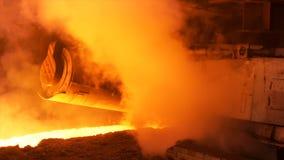 在钢铁厂的热的钢铁生产,冶金学概念 储蓄英尺长度 有流动的溶解的钢的热的商店在 图库摄影