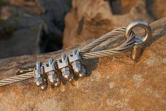 在钢索的坚实结 电烙在块固定的扭转的绳索由螺丝短冷期勾子 绳索末端细节停住入砂岩岩石 库存照片