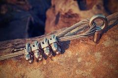 在钢索的坚实结 电烙在块固定的扭转的绳索由螺丝短冷期勾子 绳索末端细节停住入砂岩岩石 免版税图库摄影