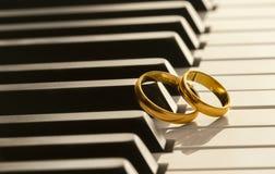 在钢琴的婚戒 免版税库存照片