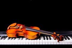 在钢琴的小提琴 免版税库存照片