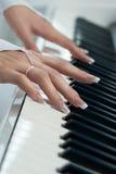 在钢琴的钥匙的女性手 库存图片
