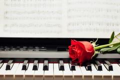 在钢琴钥匙和乐谱的红色玫瑰 免版税库存照片