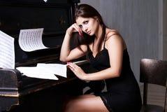 在钢琴附近的哀伤的女孩 免版税库存图片