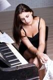 在钢琴附近的哀伤的女孩 库存照片