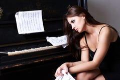在钢琴附近的哀伤的女孩 免版税图库摄影