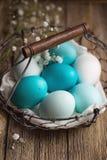 在铁丝网筐的被洗染的复活节彩蛋 免版税库存图片