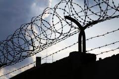 在铁丝网篱芭后的剧烈的云彩在监狱墙壁上 库存图片