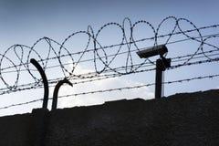 在铁丝网篱芭后的安全监控相机在监狱墙壁附近 免版税图库摄影