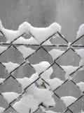 在铁丝网篱芭捉住的雪 免版税库存图片