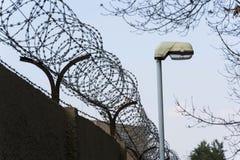 在铁丝网篱芭旁边的街灯在监狱墙壁附近舒展了 免版税库存照片