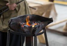 在铁匠铺与波浪边缘的金属融解伪造的明亮的橙色火焰  库存图片
