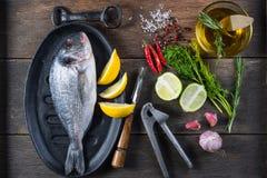在铁土气平底锅的新鲜的整个海鱼,烹调概念 图库摄影