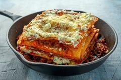 在铁平底锅的自创酥脆烤宽面条用剁碎的牛肉博洛涅塞调味汁,帕尔马干酪 库存照片