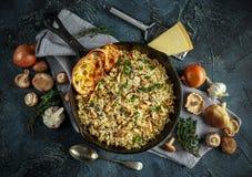 在铁平底锅的蘑菇意大利煨饭用草本和帕尔马干酪 免版税图库摄影