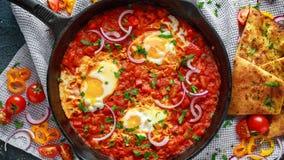 在铁平底锅的鲜美早餐Shakshuka 煎蛋用蕃茄,红色,黄色胡椒,葱,荷兰芹,皮塔饼面包和 图库摄影