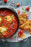 在铁平底锅的鲜美早餐Shakshuka 煎蛋用蕃茄,红色,黄色胡椒,葱,荷兰芹,皮塔饼面包和 库存照片