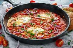在铁平底锅的鲜美早餐Shakshuka 煎蛋用蕃茄,红色,黄色胡椒,葱,荷兰芹,皮塔饼面包和 免版税库存图片