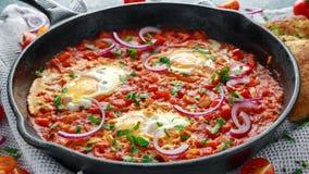 在铁平底锅的鲜美早餐Shakshuka 煎蛋用蕃茄,红色,黄色胡椒,葱,荷兰芹,皮塔饼面包和 免版税库存照片