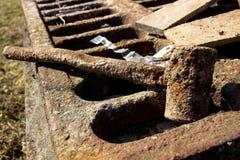 在铁格栅的生锈的锤子 免版税库存图片