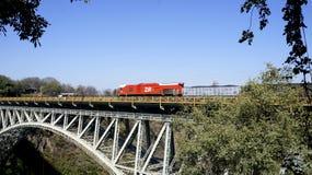 在铁桥梁的红色火车,津巴布韦,非洲 库存图片