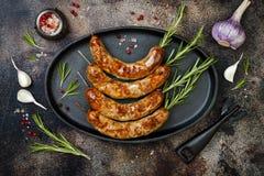 在铁煎锅的烤自创迷迭香香肠串在土气黑暗的石厨房用桌 顶视图,平的位置 库存图片