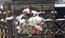 在铁篱芭的花在雕象附近 免版税库存照片