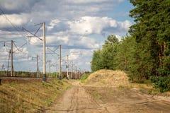 在铁路有电轴承pollars的和杉木森林传送带之间的农村含沙路有在背景的多云秋天天空的 免版税图库摄影