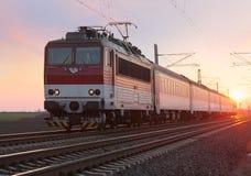 在铁路的旅客列车在日落 免版税图库摄影