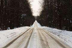 在铁路路附近的城市发光雪星期日对冬天木头 并且刹车从轮胎的紧急状态踪影 免版税库存照片