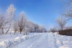 在铁路路附近的城市发光雪星期日对冬天木头 库存图片