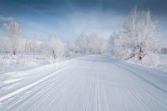 在铁路路附近的城市发光雪星期日对冬天木头 免版税库存图片
