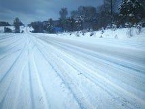 在铁路路附近的城市发光雪星期日对冬天木头 免版税库存照片