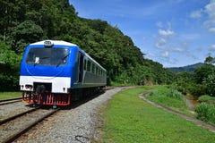 在铁路轨道旁边训练运输服务在与河的农村热带区域 免版税库存图片