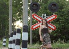 在铁路s符号业务量附近的女孩 图库摄影