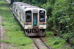 在铁轨的白色火车 当绿色树围拢方式 从日本的使用的小火车 库存图片
