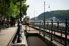 在铁锁式桥梁附近的黄色电车在布达佩斯 免版税库存照片