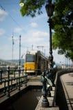 在铁锁式桥梁附近的黄色电车在布达佩斯 库存照片
