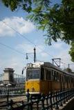 在铁锁式桥梁附近的黄色电车在布达佩斯 免版税库存图片