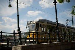 在铁锁式桥梁附近的黄色电车在布达佩斯 库存图片
